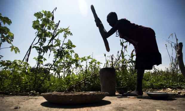 A woman mills sorghum from her family's land in northern Bahr El-Ghazal in a drought-stricken South Sudan in 2015. Photograph: Albert Gonzalez Farran/AFP/Getty Images