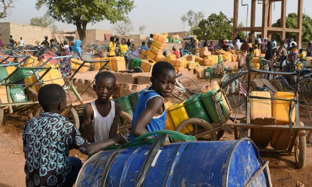 Children wait to buy water in Ouagadougou, Burkina Faso, one of the countries most at risk from ecological threats. Photograph: Anne Mimault/Reuters